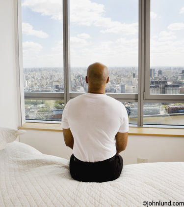 Man Sitting On Hotel Room Bed